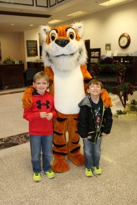 Children standing with tiger mascot